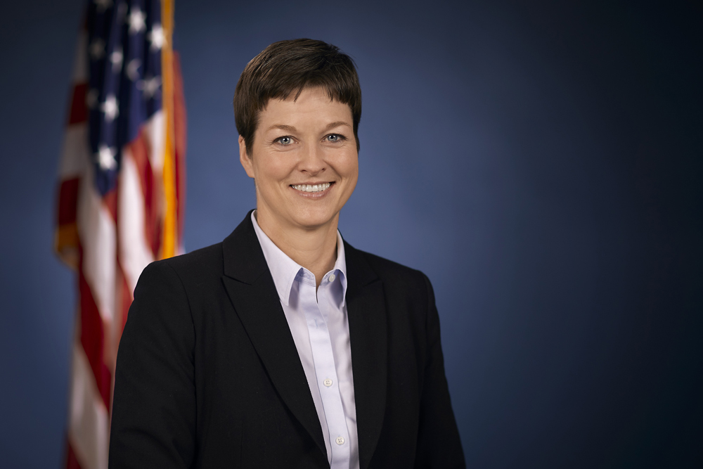 Portrait photo of Secretary Teresa Miller smiling and standing in front of the US flag.